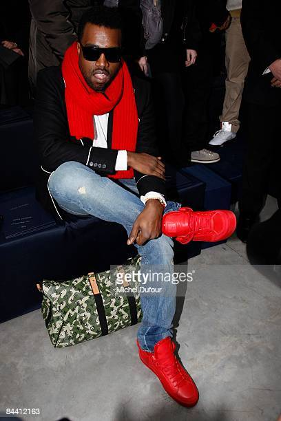 Kanye West wears red Louis Vuitton shoes that he designed at the Louis Vuitton fashion show during Paris Fashion Week Menswear Autumn/Winter 2009 on...