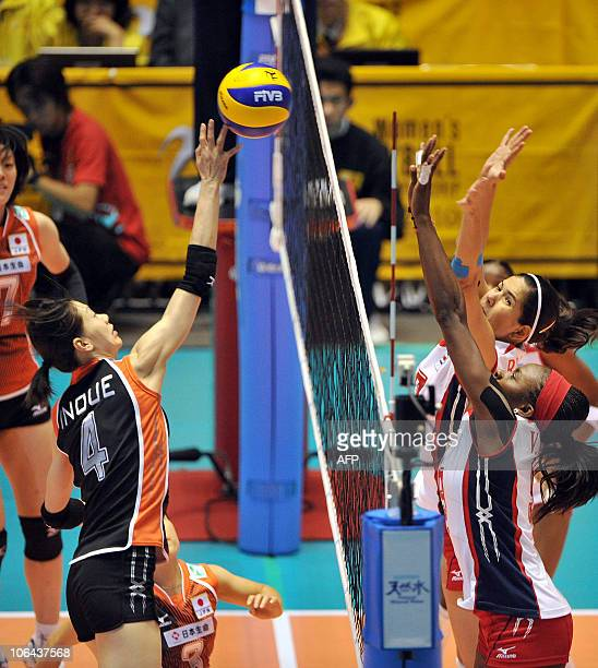 Kaori Inoue of Japan spikes the ball as Verania Willis and Paola Ramirez Vargas of Costa Rica defend during their first round match of the women's...