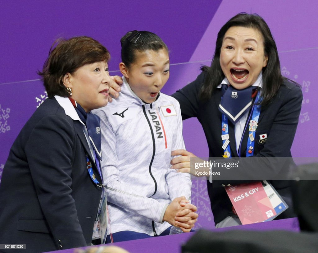 Kaori Sakamoto (C) of Japan reacts after seeing her score in the women's figure skating short program along with her coaches at the Pyeongchang Winter Olympics in Gangneung, South Korea, on Feb. 21, 2018. ==Kyodo