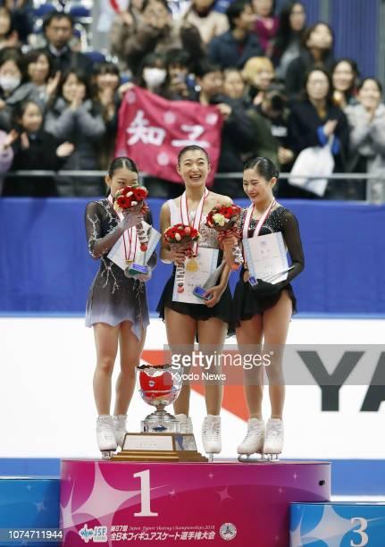 Kaori Sakamoto poses after winning Japan's national figure skating championships alongside silver medalist Rika Kihira and bronze medalist Satoko...