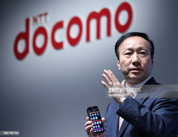 Kaoru Kato, president and chief executive officer of NTT DoCoMo Inc., holds a Galaxy S4 smartphone manufactured by Samsung Electronics Co. As he...