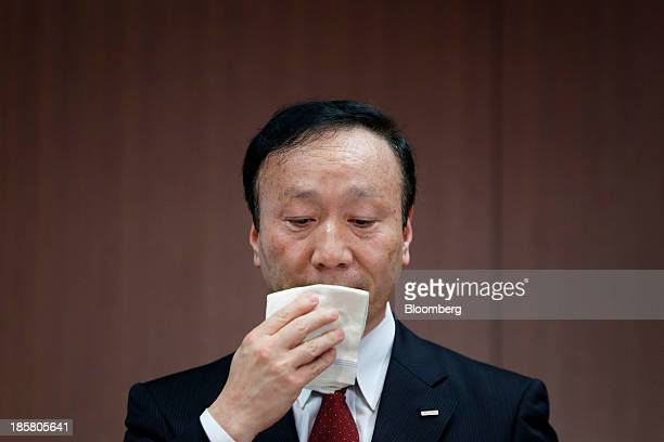 Kaoru Kato president and chief executive officer of NTT Docomo Inc uses a handkerchief to wipe his face during a news conference in Tokyo Japan on...