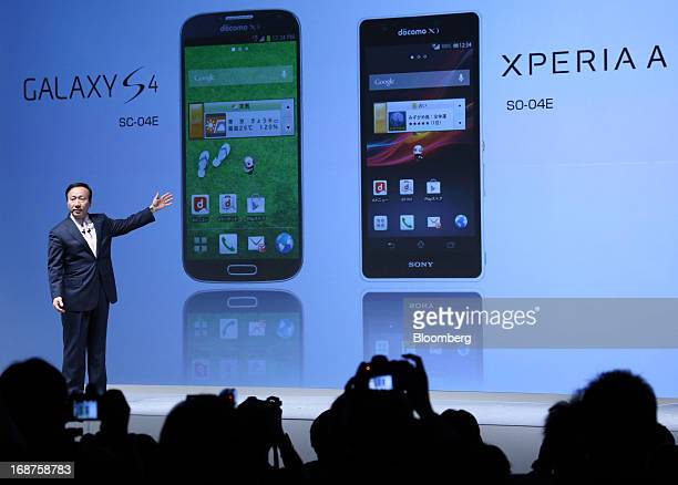 Kaoru Kato, president and chief executive officer of NTT DoCoMo Inc., speaks in front of images of the Galaxy S4 smartphone manufactured by Samsung...