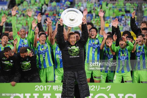 Kaoru Takayama of Shonan Bellmare lifts the trophy as they celerbrate J2 champions and promotion to J1 after the J.League J2 match between Shonan...