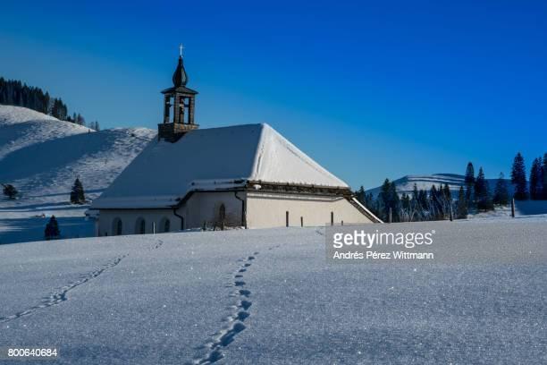 Kapelle im Gegenlicht in den bayrischen Alpen mit Baumbestand