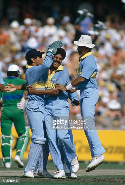 Kapil Dev of India is congratulated by wicketkeeper Sadanand Viswanath and team-mates after bowling Pakistan batsman Qasim Umar first ball during the...