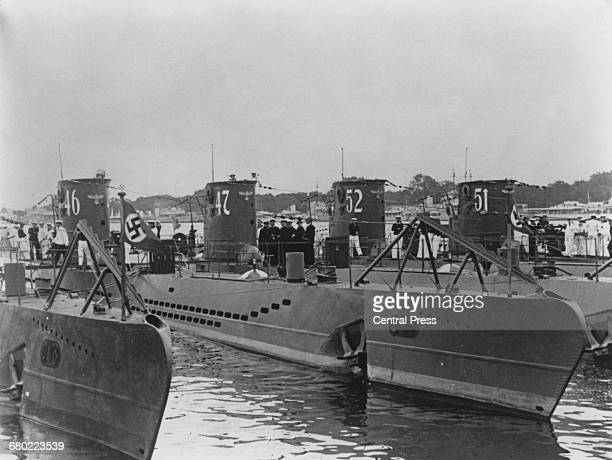 Kapitanleutnant Gunther Prien and his officers gather on the deck of the U47 a Type VIIB Uboat submarine of the German navy while tied up alongside...