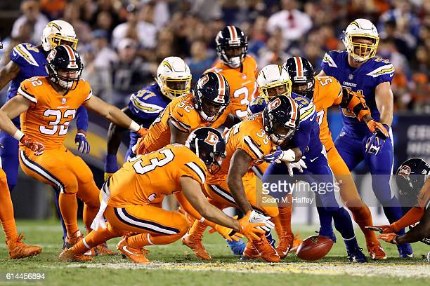 Kapri Bibbs Andy Janovich and Corey Nelson of the Denver Broncos lunge to recover a fumble during the second half of a game against the San Diego...