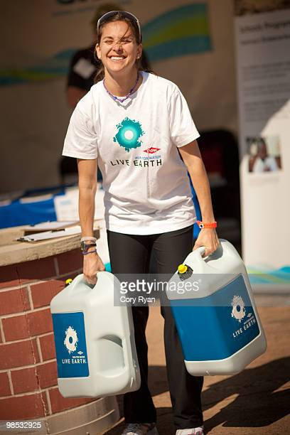 Kara Goucher lifts jugs full of water at the Dow Live Earth Run for Water at Lake Nokomis on April 18 2010 in Minneapolis Minnesota