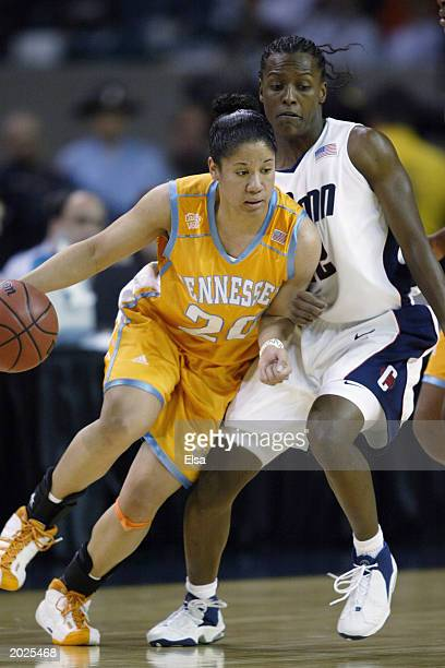 Kara Lawson of the University of Tennessee Lady Volunteers drives around Ashley Battle of Connecticut Huskies during the NCAA Women's Championship...