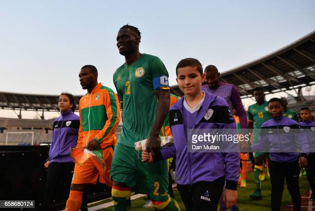 Kara Mbodj of Senegal leads out his team prior to the International Friendly match between the Ivory Coast and Senegal at the Stade Charlety on March...