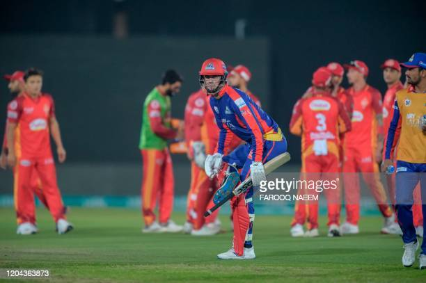 Karachi Kings Alex Hales and Islamabad United players wait for the third umpire decision as he successfully stumps out Islamabad United wicketkeeper...