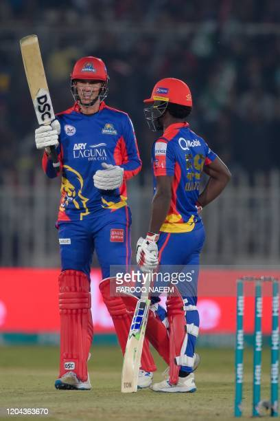 Karachi Kings Alex Hales raises his bat after his half century next to Chadwick Walton during the Pakistan Super League T20 cricket match between...