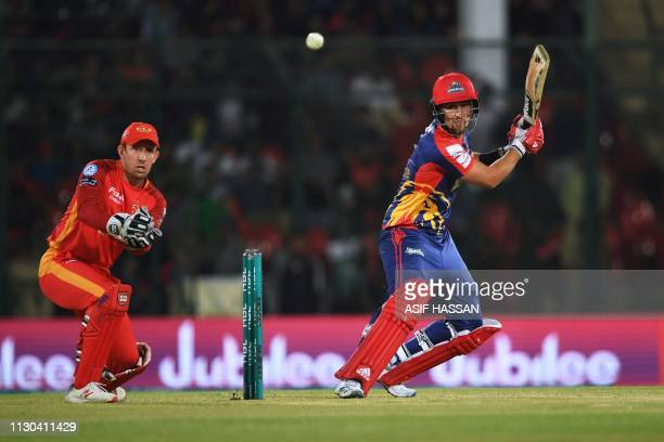 Karachi Kings cricketer Kiam Livingstone plays a shot as Islamabad United wicketkeeper Luke Ronchi looks on during the elimination match between the...