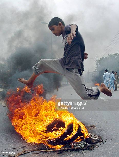 A Pakistani boy jumps over burning tyres during a demonstration in Karachi 27 August 2006 against the killing of tribal rebel chieftain Nawab Akbar...