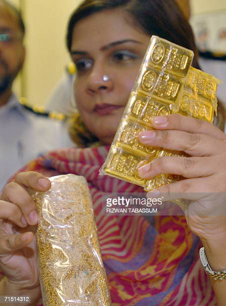 A Pakistani female custom official shows seized packets of gold and jewelry during a press conference in Karachi 25 July 2006 Pakistani custom...
