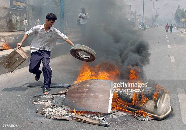 A Pakistani man places a tyre on a protest bonfire in the middle of the street during a demonstration in Karachi 27 August 2006 against the killing...