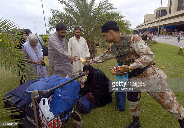 A Pakistani paramilitary soldier distributes food items to passengers at the Jinnah International airport in Karachi 12 May 2007 after flights were...