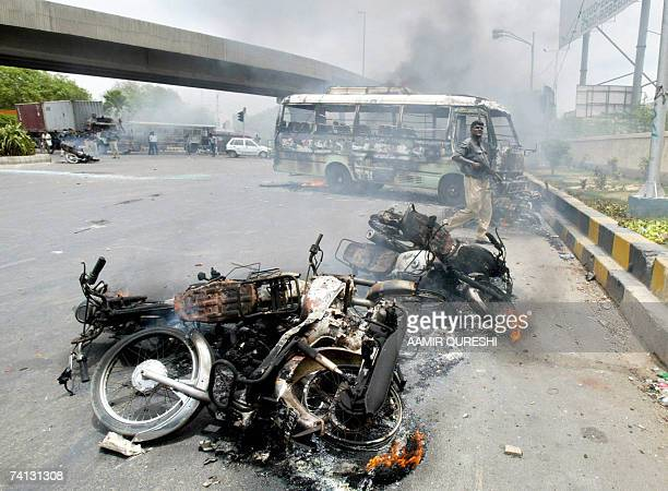 A Pakistani policeman passes by burning vehicles during clashes which erupted between the government and oppositions parties supporters in Karachi 12...