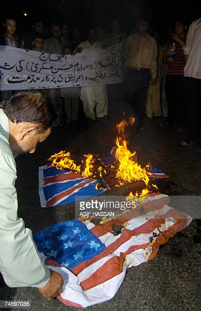 A Pakistani Shiite Muslim torches US flags during a protest in Karachi 14 June 2007 to denounce an attack on Imam AlAskari Mosque at Samarra in Iraq...