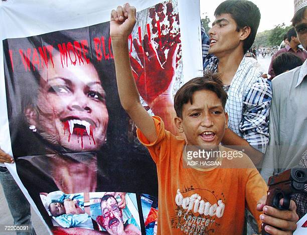 A Pakistani Shiite Muslim young boy holds a toy gun as others carry a picture of US Secretary of State Condoleezza Rice during a protest on AlQuds...