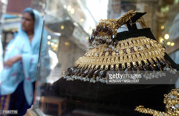 A Pakistani woman walks past a gold necklace displayed at a jewelery shop in Karachi 26 May 2006 Worldwide gold demand fell 16 percent in the first...