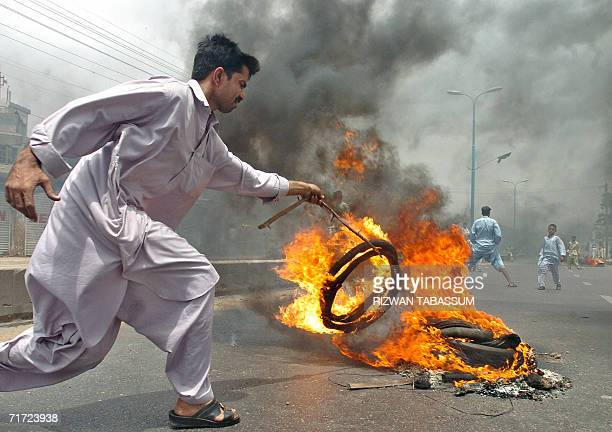 A young Pakistani man adds fuel to the fire in the middle of the street during a demonstration in Karachi 27 August 2006 against the killing of...