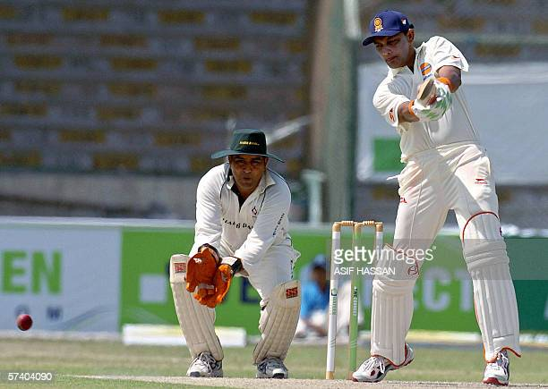 Former Indian cricket captain Mohammad Azharuddin plays a shot as Pakistani wicketkeeper Azam Khan looks on during the first One Day match of a four...