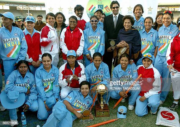 Former Pakistani cricket team captain Wasim Akram and members of the Indian women's cricket team pose with the Asia Cup trophy after India defeated...
