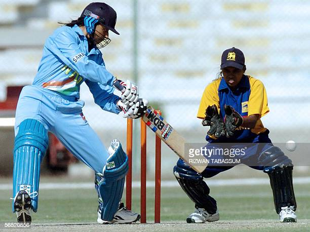 Indian women's cricketer Anjum Chopra plays a cover drive shot Sri Lankan wicketkeeper Dumila Dedunu looks on during the final match between India...