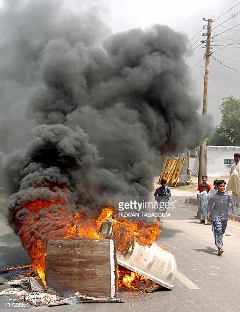 Pakistani children walk past wood burning in the street after it was set on fire by protesters in Karachi 27 August 2006 against the killing of...