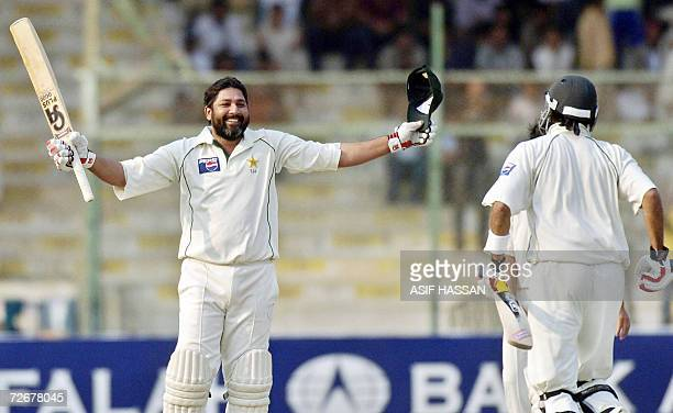 Pakistani cricket team captain Inzamam-ul-Haq waves his bat and helmet after scoring a half century against West Indies during the fourth day of the...
