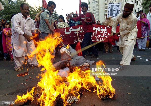 Pakistani Labour Party activists beat burning effigies of the President Pervez Musharraf and US President George W Bush during the May Day rally in...