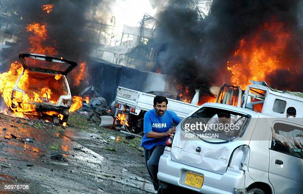 Pakistani people push a car past burning vehicles after a twin bomb blast outside a five star hotel in Karachi 02 March 2006 Two car bombs exploded...