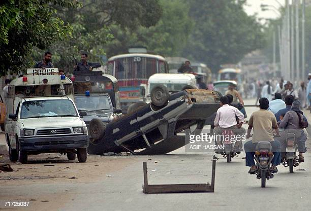 Pakistani police patrol vehicles manouver past cars in Karachi 27 August 2006 overturned in protest by demonstrators against the killing of tribal...