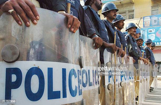 Pakistani policemen stand alert with riot shields as activists of a national alliance stage a demonstration in Karachi 31 August 2006 against the...