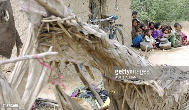 Pakistani rain affected family wait for relief out side her collapse mud house after heavy rain and thunderstorms outskirts of Karachi 25 June 2007...