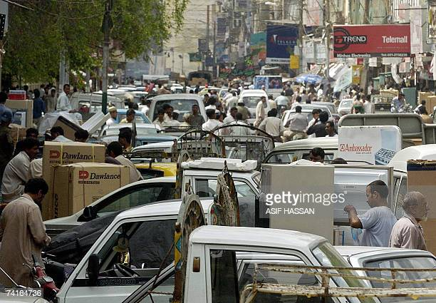 Pakistani shoppers examine goods at a crowded electronics market in Karachi 16 May 2007 on the third day after bloody clashes in the southern port...
