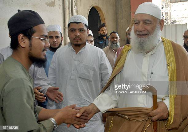 The former Imam of Palestinian Mosque Aqsa Shiekh Ahmed Mahmood Siyam shakes hands with a student of The Jamia Binoria Islamic University during his...