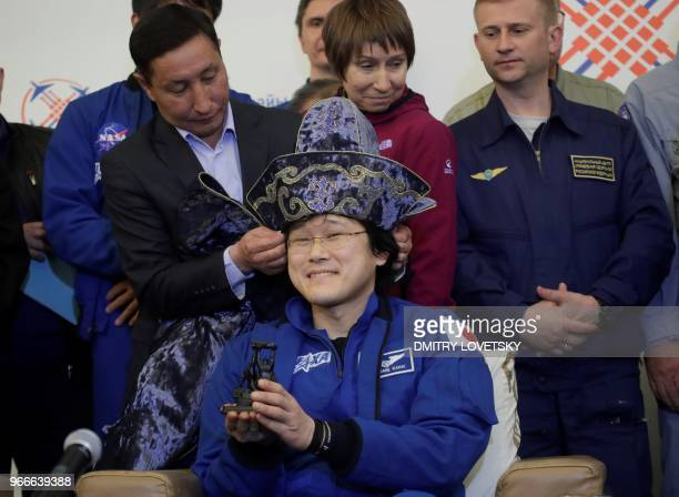 A Karaganda city official puts a Kazakh national hat on Japanese astronaut Norishige Kanai center after the landing of the Russian Soyuz MS07 space...