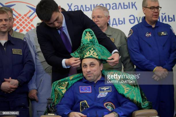 A Karaganda city official puts a Kazakh national hat on Russian cosmonaut Anton Shkaplerov after the landing of the Russian Soyuz MS07 space capsule...