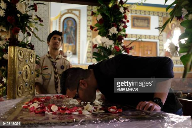 Karam Masoud, a Greek Orthodox Palestinian student from Gaza, kisses the epitaphios inside the catafalque representing Christ's tomb, after the Holy...