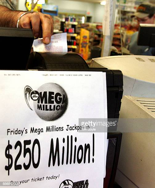 Karam Toor reaches for a customer's Mega Millions lottery ticket coming out of the printer September 16 2005 in Russell Illinois on the border of the...