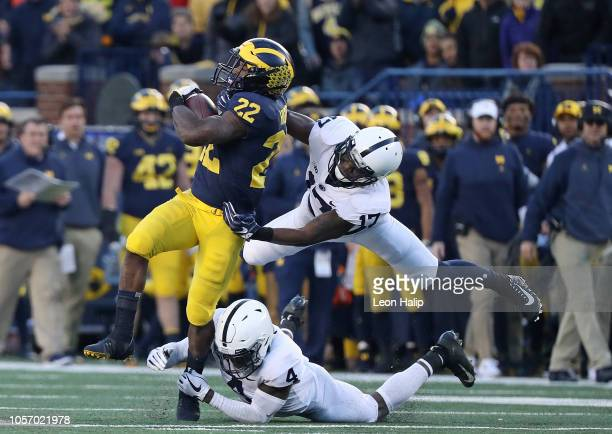 Karan Higdon of the Michigan Wolverines runs for a short gain as Garrett Taylor of the Penn State Nittany Lions makes the stop during the third...