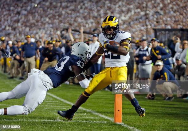 Karan Higdon of the Michigan Wolverines rushes for a 1 yard touchdown against Manny Bowen of the Penn State Nittany Lions on October 21 2017 at...