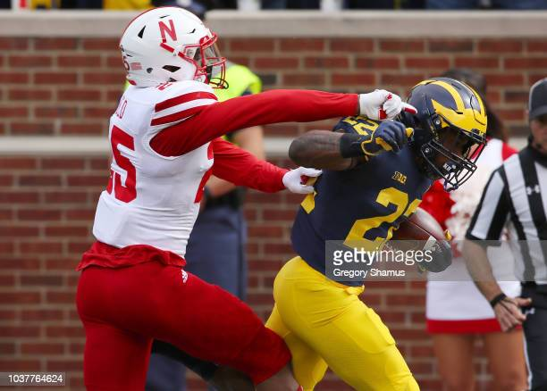 Karan Higdon of the Michigan Wolverines tries to get around Tre Neal of the Nebraska Cornhuskers during a first half run on September 22 2018 at...