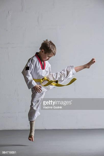 Karate boy kicking in air against white wall