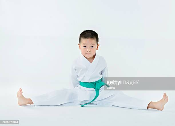 karate boy stretch - taekwondo kids stock photos and pictures