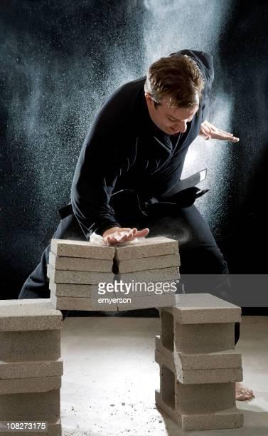 Karate-Mann gebrochen Cinder Häuserblocks