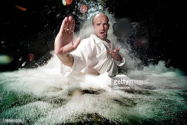 karate man practicing in a river waterfall. - artes marciais imagens e fotografias de stock